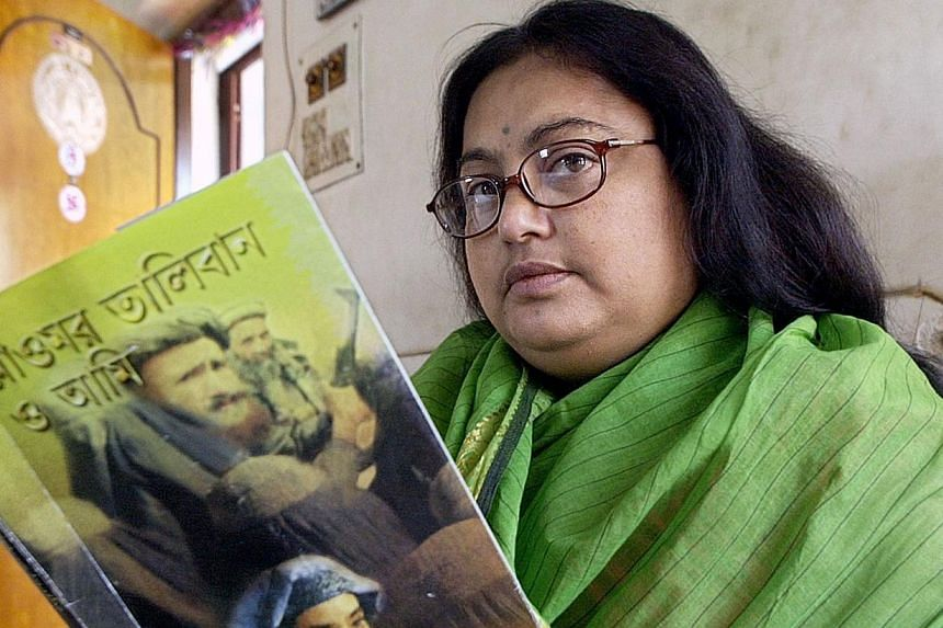 """In this photograph taken on March 6, 2003, Indian author Sushmita Banerjee holds one of her Bengali language novels """"Mollah Omar Taliban O Aami"""" (Mollah Omar, Taliban and Me) in Kolkata. Suspected Taleban militants shot dead Ms Banerjee in the easter"""