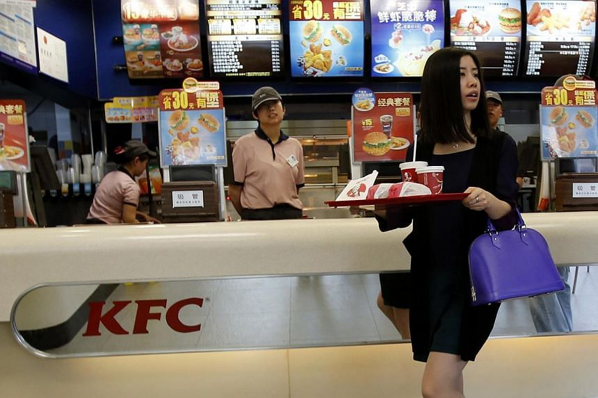 A woman carries a tray of food inside a KFC restaurant in Beijing in this May 9, 2013 file photo. KFC parent Yum Brands Inc on Friday said August sales at established restaurants in China fell an estimated 10 per cent, as it works to recov