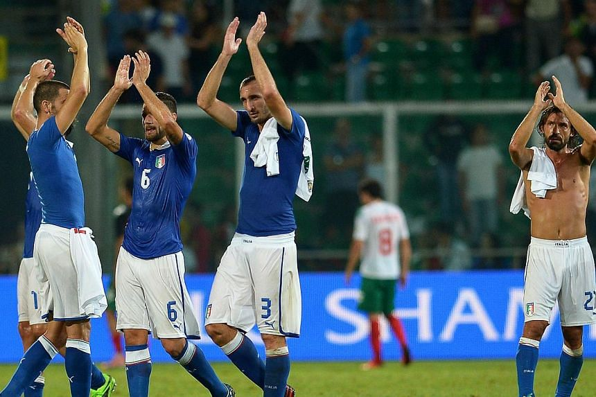 Italy's midfielder Andrea Pirlo (right), defender Giorgio Chiellini (centre) and midfielder Antonio Candreva celebrate at the end of the Fifa World Cup 2014 qualifying football match between Italy and Bulgaria on Sept 6, 2013, at the Renzo Barbera st