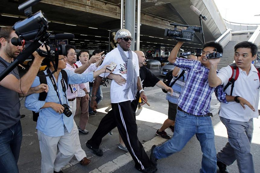 Former basketball star Dennis Rodman is followed by journalists chasing him upon his arrival at Beijing Capital International Airport on Sept 7, 2013. Rodman returned to China on Saturday from his second visit to North Korea this year where he again