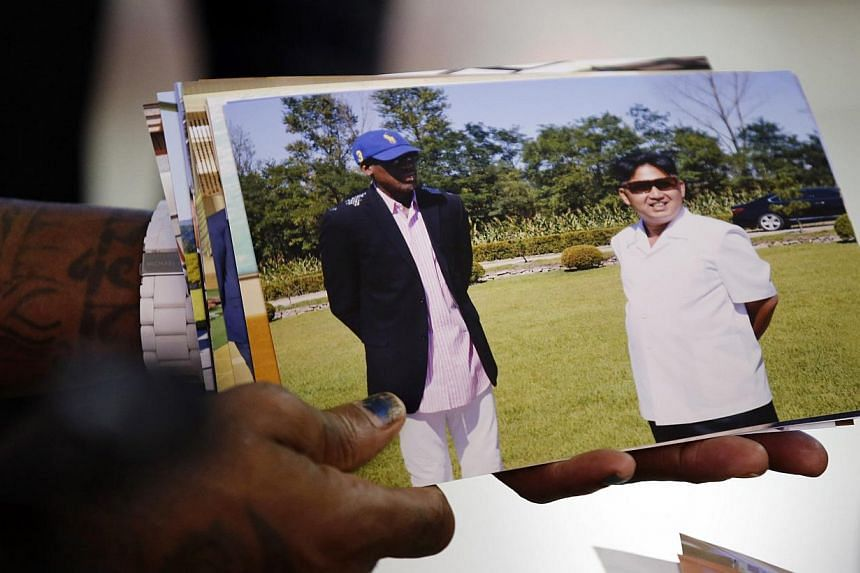 Former basketball star Dennis Rodman shows a picture, which he took with North Korean leader Kim Jong Un, as he arrives at Beijing Capital International Airport on Sept 7, 2013. Rodman returned to China on Saturday from his second visit to North Kore