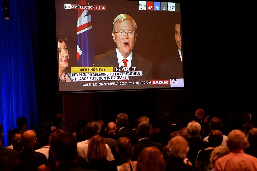 Supporters of conservative challenger Tony Abbott watch Australian Prime Minister Kevin Rudd's address on a screen in Sydney on Saturday, Sept 7, 2013. Mr Rudd announced he would step down as Labor chief after a heavy defeat to the conservatives