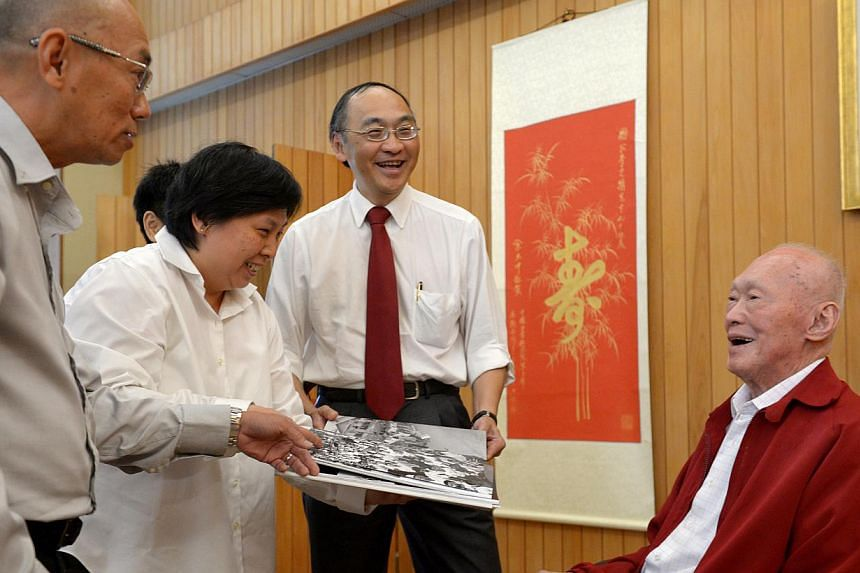(From left) SPH English and Malay Newspapers Division managing director Han Fook Kwang, Straits Times picture editor Stephanie Yeow, Lianhe Zaobao news editor Han Yong May (hidden) and SPH chief executive Alan Chan presenting the book to Mr Lee Kuan