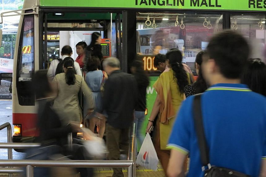 BUS SERVICE 106 - SHORTER WAITING TIMES...: Commuters boarding service 106 at Bukit Batok bus interchange. Peak-hour waiting times have been cut to seven minutes. Some said it took as long as 20 minutes before. -- ST PHOTO: YEO SAM JO