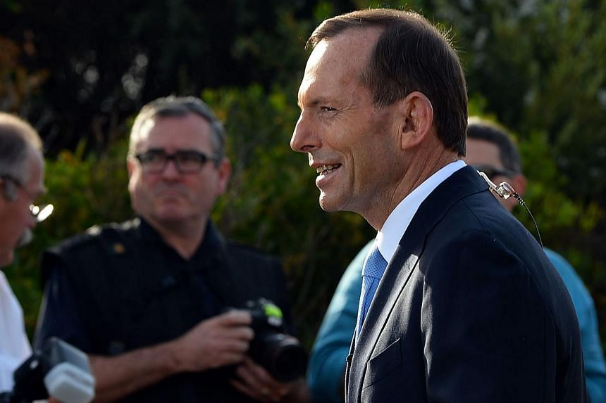 Australian opposition leader Tony Abbott waits for his live interview outside a polling station in Sydney on Saturday Sept 7, 2013. Early exit polls taken in Australia's national election on Saturday showed the Abbott-led conservative opposition romp