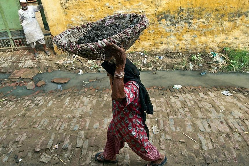 In this picture taken on August 10, 2012, 60-year-old manual scavenger Kela is seen carrying a basket of human excrement on her head after cleaning toilets in Nekpur village, Muradnagar in Uttar Pradesh, some 40km east of New Delhi. Indian lawmakers