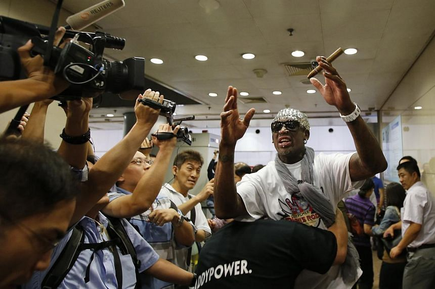 Former basketball star Dennis Rodman gesturing as he talks to journalists chasing him upon his arrival at Beijing Capital International Airport on September 7, 2013. Rodman returned on Saturday from his second visit to North Korea this year where he