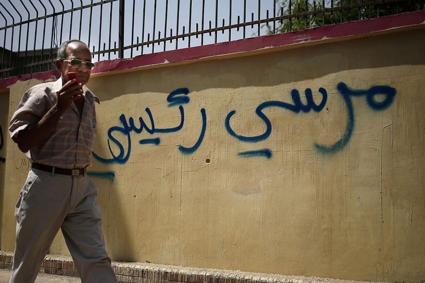 An Egyptian man walks by a graffiti in Arabic that reads, Mursi My President, referring to the ousted Egyptian President Mohammed Mursi, in Cairo, Egypt on Sunday, Sept 8, 2013.Egyptian military helicopters carried out a second day of air raids