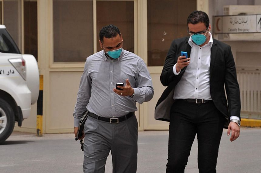 Egyptian medical workers wearing masks as they leave the emergency section in King Fahad hospital in the city of Hofuf on June 16, 2013, 370km East of the Saudi capital Riyadh. Another three people have died in Saudi Arabia after contracting the Mers