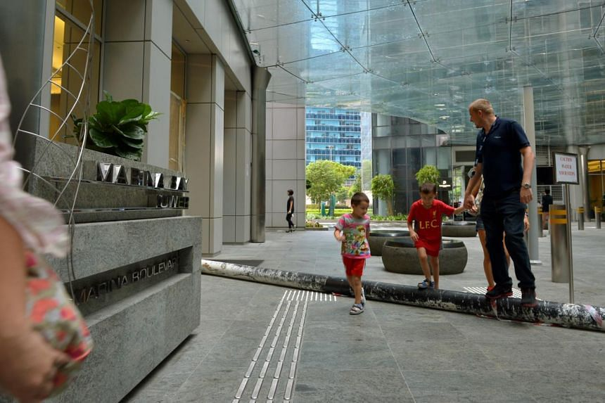 Residents stepping over a temporary pipe laid across the path near the taxi stand at The Sail@Marina Bay. The pipe had to be put up to supply water to one of the two towers after an underground pipe burst in April. -- ST PHOTO: KUA CHEE SIONG