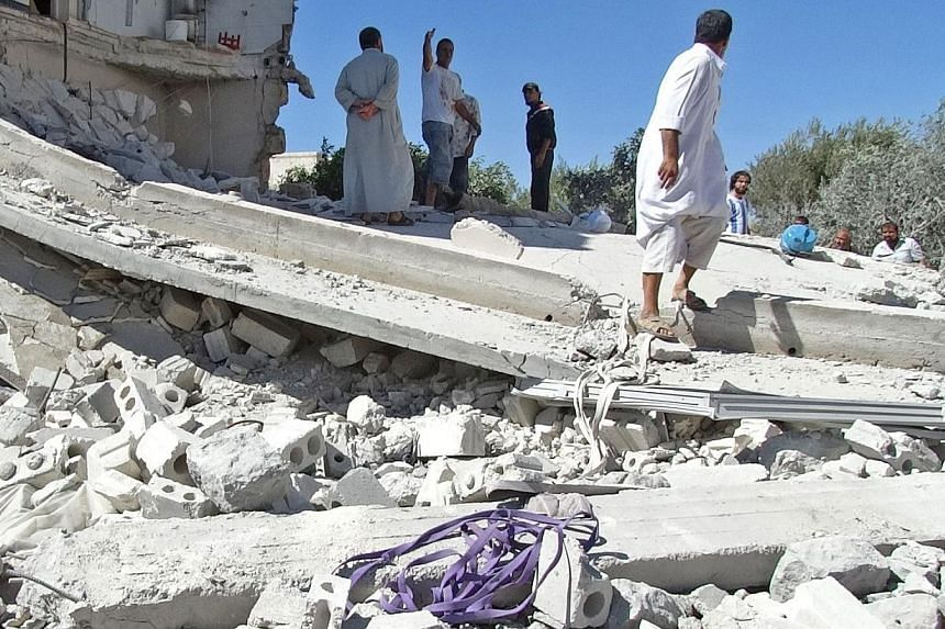 Men gather on the remains of a destroyed building after reported air strikes by Syrian government forces in the rebel-held northwestern Syrian province of Idlib on Thursday, Sept 5, 2013.The Pentagon is readying more intense and longer attacks
