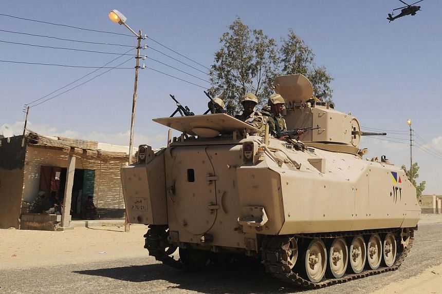 Egyptian Army soldiers patrol in an armored vehicle backed by a helicopter gunship during a sweep through villages in Sheikh Zuweyid, northern Sinai, Egypt. At least 10 people were killed as Egypt's army launched an air and ground assault on Sinai mi