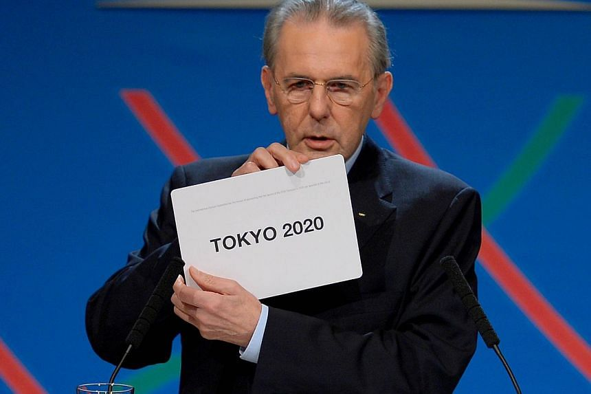 """IOC President Jacques Rogge shows the card reading """"Tokyo"""" as he announces the winner of the bid to host the 2020 Summer Olympic Games, during the 125th session of the International Olympic Committee (IOC), in Buenos Aires, on Sept 7, 2013. The finan"""