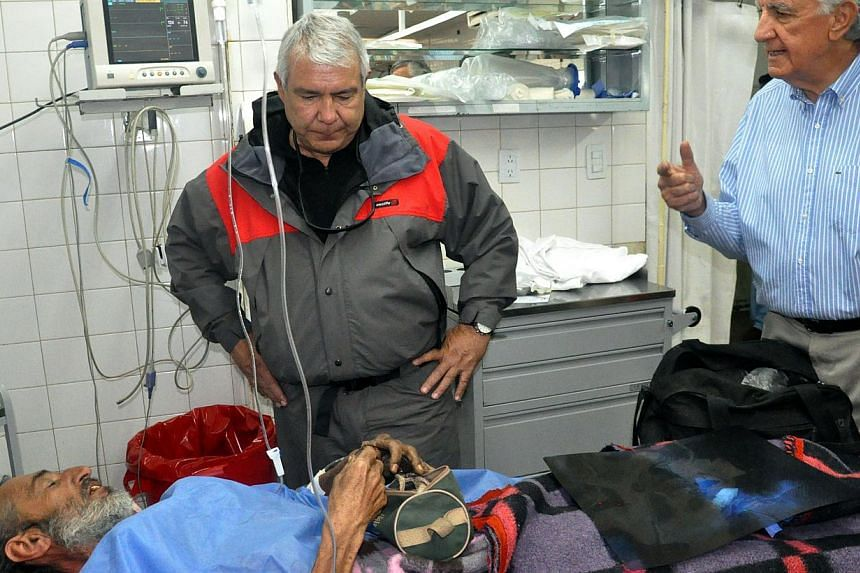 Handout photo released by the San Juan provincial Government of San Juan's Governor Jose Luis Gioja (right) as he speaks with Uruguayan Raul Gomez Cincunegui (bottom) at the Rawson hospital in San Juan, Argentina on Sept 8, 2013. A 58-year-old Urugua