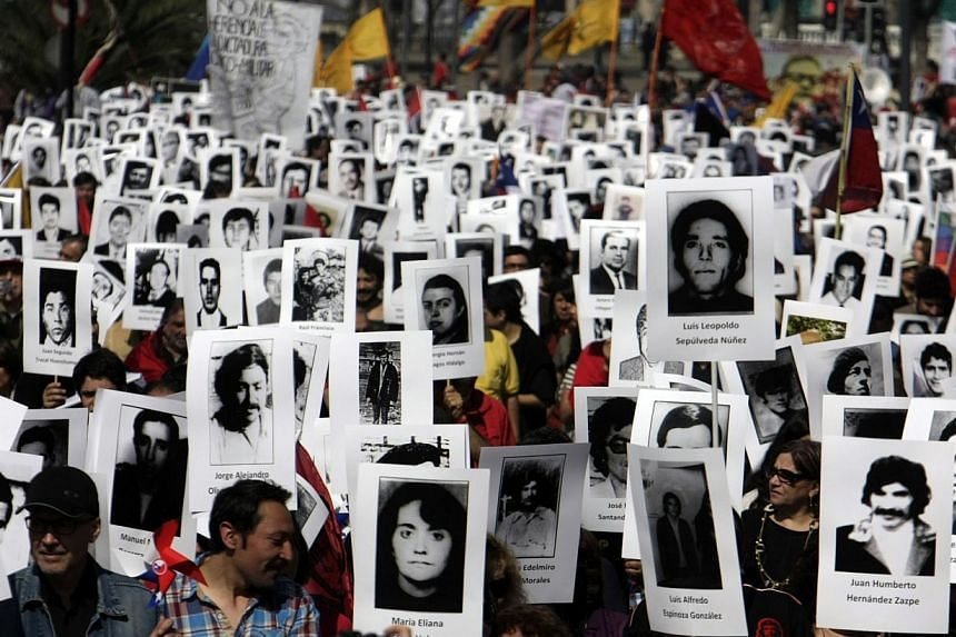 "Activists of the Chilean Human Rights organization ""Detained and Disappeared People"" take part in a demonstration in Santiago on Sept 8, 2013, in remembrance of late President (1970-1973) Salvador Allende, who died on Sept 11, 1973 during the militar"