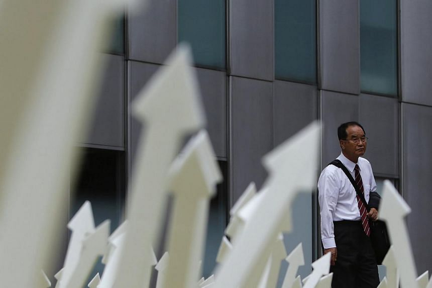 A man walks past an artwork displayed in Tokyo's business district on Sept 8, 2013. Japan's economy in the April-June quarter expanded more than initially estimated, revised data showed on Monday, offering another boost for Tokyo's bid to reverse yea