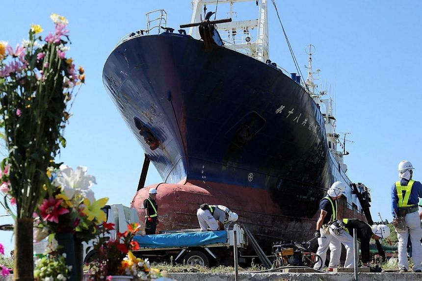 Workers prepare for scrapping the large fishing boat, No.18 Kyotoku-maru, which was swept far inland by the 2011 tsunami in Kesennuma city in Miyagi prefecture, northern Japan on Sept 9, 2013. -- PHOTO: AFP