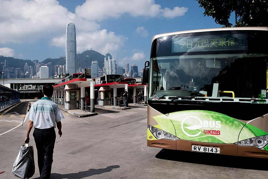 A man walks past an electric bus in Hong Kong on Monday, Sept 9, 2013. Hong Kong's first battery-powered public bus took to the streets on Monday as part of a drive against the city's choking pollution. -- PHOTO: AFP