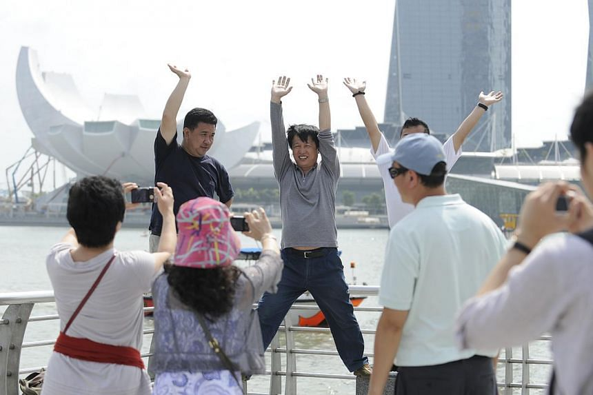 Tourists from China posing for a photograph with the Marina Bay Sands resort in the background. Local travel players have mixed reactions to