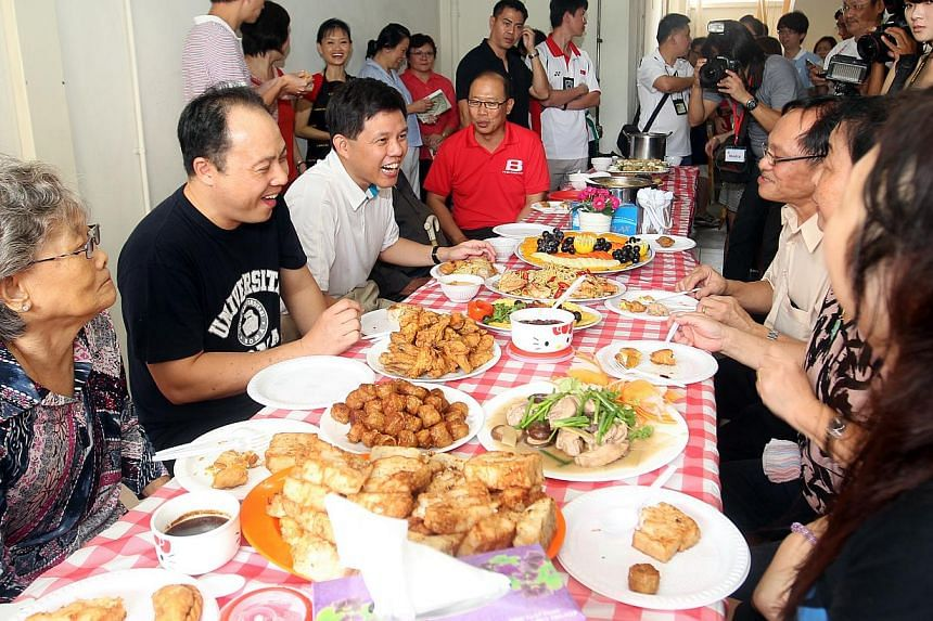 Mr Chan Chun Sing (third from left) with (clockwise from left) Ms Chian Soh Moy, 81, Mr Kelvin Seow, 46, Jurong GRC MP David Ong, Mr Tia Jee Aik, 60, Ms Ho Kim Tin, 58, and Ms Charlynn Ng, 41, at a potluck party in Bukit Batok yesterday.
