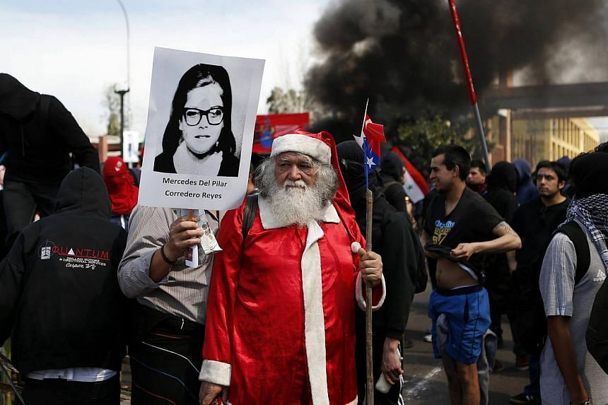 A demonstrator dressed as Santa Claus is seen during a protest marking the 1973 military coup in Santiago Sept 8, 2013. The 40th anniversary of the coup d'etat that ushered in a 17-year dictatorship under General Augusto Pinochet will be marked on Se