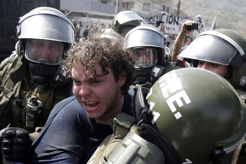 A man is arrested by riot policemen during a demonstration in Santiago on Sept 8, 2013, in remembrance of late President (1970-1973) Salvador Allende, who died on Sept 11, 1973 during the military coup d'etat led by general Augusto Pinochet. On Sept