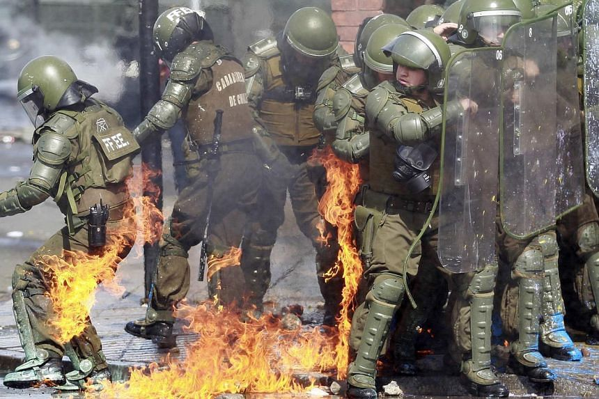A riot policeman catches fire from a molotov cocktail bomb during a protest marking the 1973 military coup in Santiago, Sept 8, 2013. Sept 11 marks the 40th anniversary of the coup d'etat in Chile that ushered in a 17-year dictatorship under General