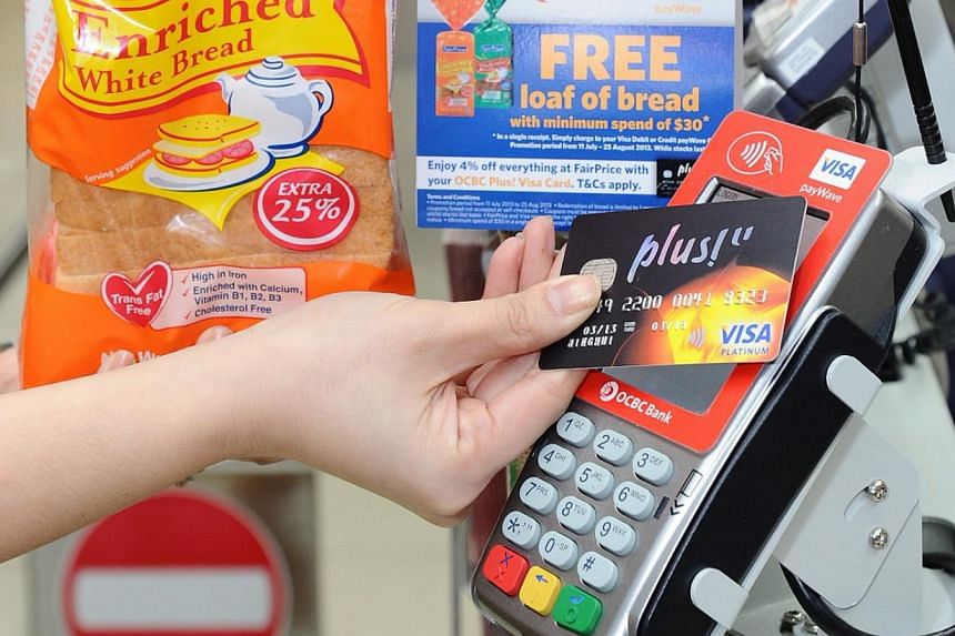 A customer using the Visa PayWave, a cashless form of payment at NTUC FairPrice. Singaporeans made more than one million transactions in August using Visa payWave, a technology which allows people to pay for goods by waving it over a contactless read