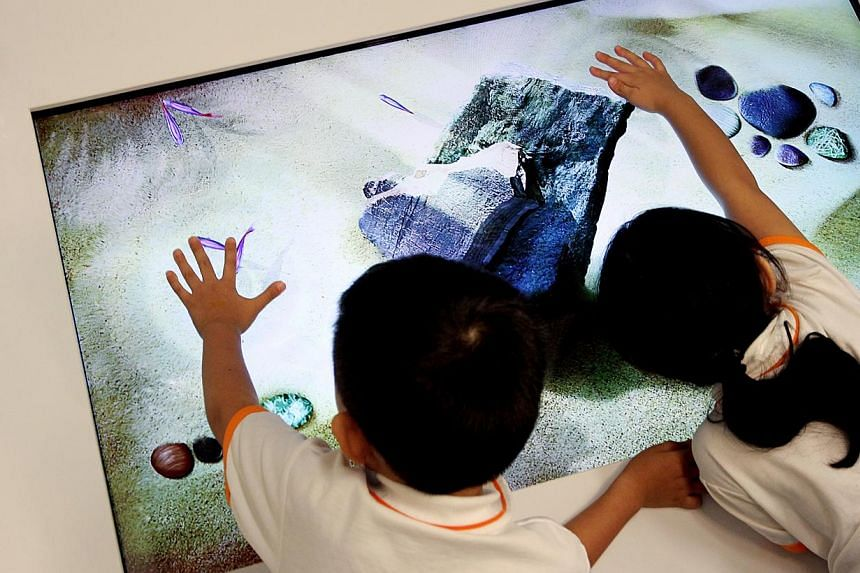 Two children play an interactive game on a touch-screen tabletop at My First Skool at Holland Drive on Aug 18 2011.Childcare centre operator NTUC First Campus and local philanthropic organisation Lien Foundation are opening a model childcare ce
