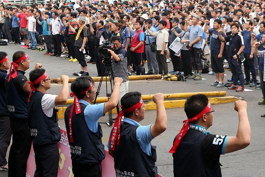 Workers from Hyundai Motor's labour union shout slogans during a partial strike at the company's main factory in Ulsan, south-east of Seoul, on Aug 20, 2013. Hyundai Motor workers have agreed a wage deal, ending a series of strikes that have cost Sou