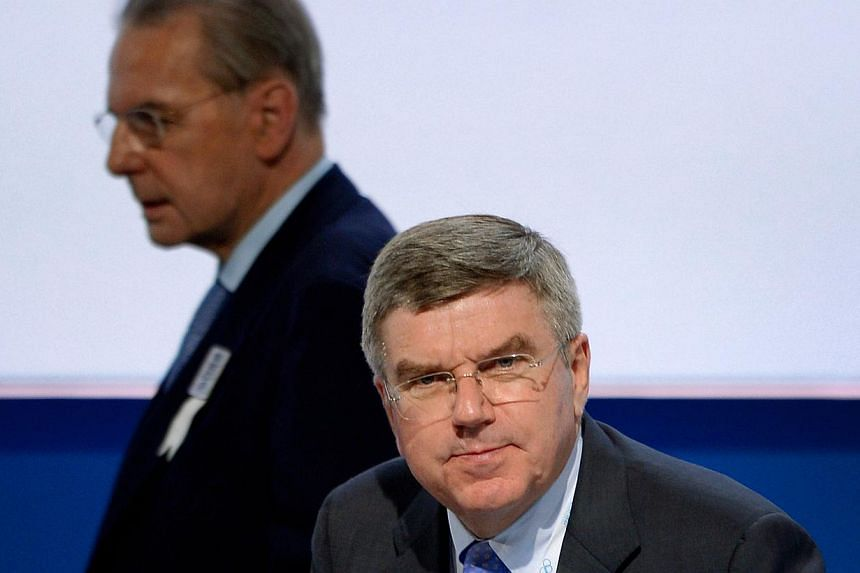 International Olympic Committee (IOC) presidency candidate German lawyer's and IOC Vice-President Thomas Bach (centre) looks on as outgoing IOC president Jacques Rogge passes behind during the IOC's 125th Session, in Buenos Aires, on Sept 8, 2013.&nb
