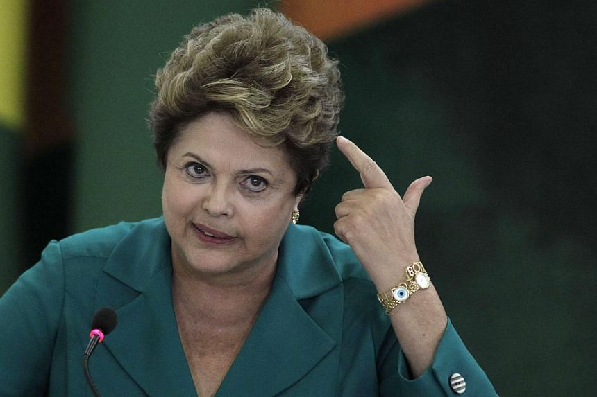 "Brazil's President Dilma Rousseff attends a ceremony at the Planalto presidential palace, in Brasilia, Brazil, Monday, Sept 9, 2013. Mrs Rousseff has accused the United States of spying on oil giant Petrobras for its own ""economic and strategic"" reas"