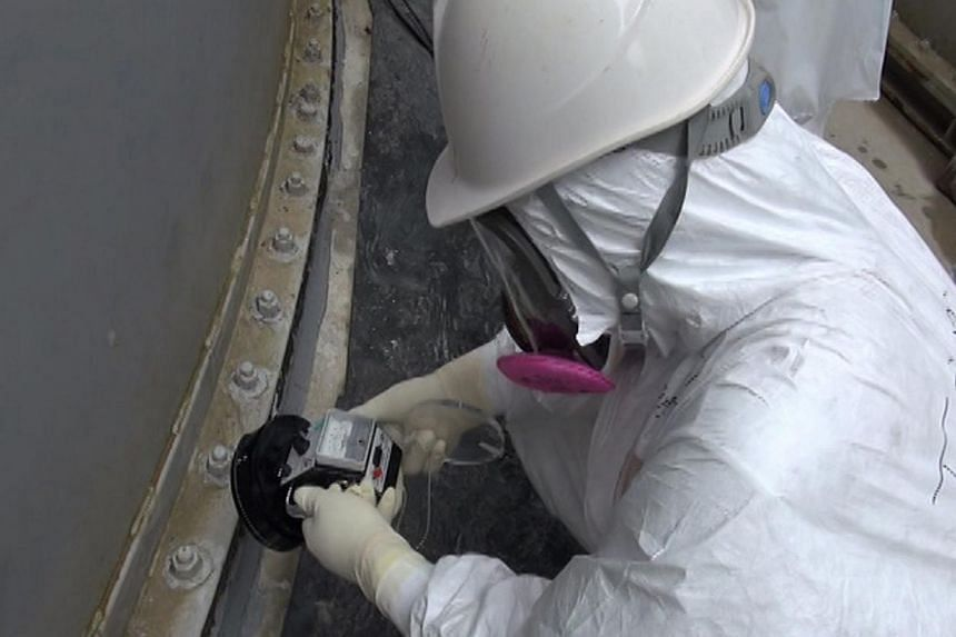This handout picture taken by Tokyo Electric Power Co (Tepco) on Sept 4, 2013 shows a Tepco worker checking radiation around the contamination water tank at Tepco's Fukushima Dai-ichi nuclear power plant at Okuma town in Fukushima prefecture. -- FILE