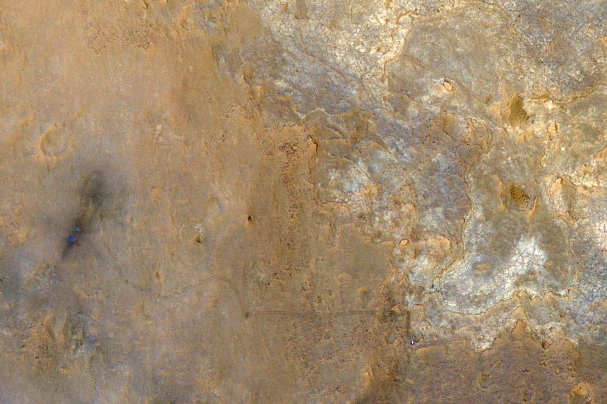 Nasa's Mars Science Laboratory rover Curiosity appears as a bluish dot near the lower right corner of this enhanced-colour view from the High Resolution Imaging Science Experiment (HiRISE) camera on Nasa's Mars Reconnaissance Orbiter taken on June 27