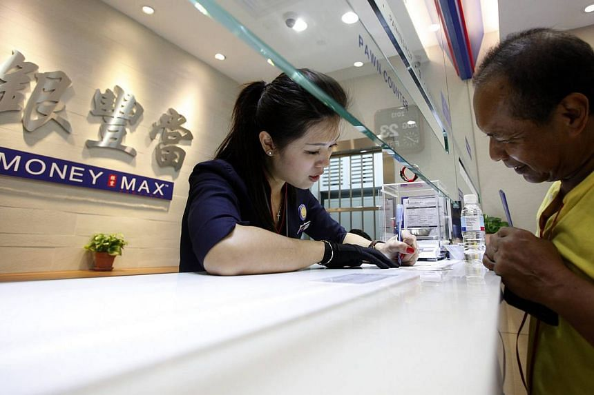 Valuer Eve Chong attends to a customer at a MoneyMax pawnshop outlet in Singapore on Aug 23, 2013. Faced with rising living costs and unable to wait until pay day, growing numbers of South-east Asians are putting their gold jewellery and designer wat