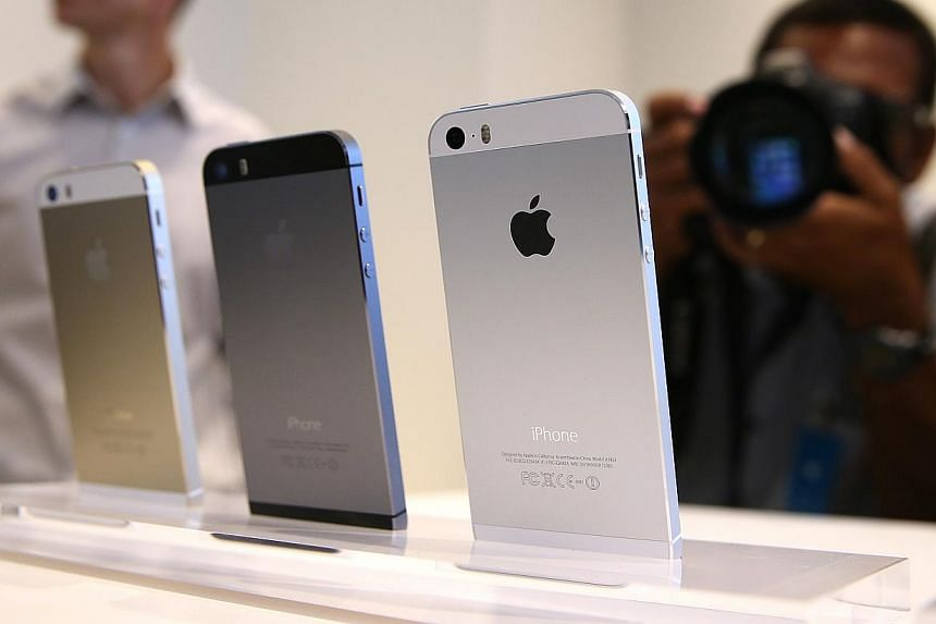 The new iPhone 5S is displayed during an Apple product announcement at the Apple campus on Sept 10, 2013 in Cupertino, California.-- PHOTO: AFP