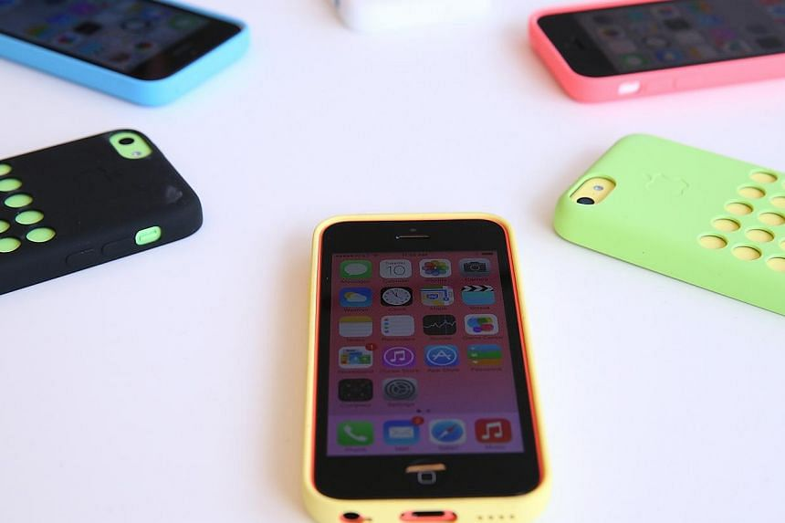 The new iPhone 5C is displayed during an Apple product announcement at the Apple campus on Sept 10, 2013 in Cupertino, California.-- PHOTO: AFP