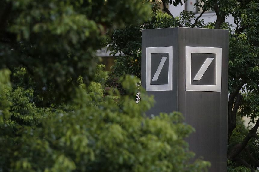 Logos of Deutsche Bank AG are seen in Tokyo on Monday, Sept 9, 2013. Japan's securities market watchdog is investigating whether Deutsche Bank AG employees provided excessive entertainment to Japanese pension fund executives in breach of regulat