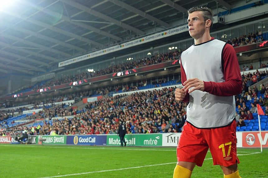 Wales midfielder Gareth Bale warms up on the touchline during the start of the World Cup 2014 European Zone group A qualifying football match between Wales and Serbia at Cardiff City Stadium in south Wales, on Tuesday, Sept 10, 2013. Wales footb