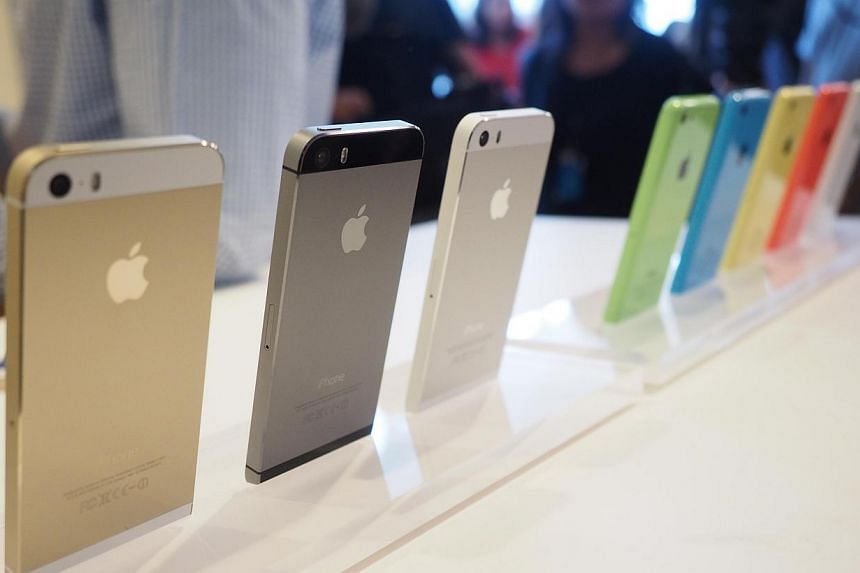 The models of the iPhone 5s (left) and the iPhone 5c being shown off during the media event at the Apple Town Hall in Cupertino. -- ST PHOTO: TREVOR TAN