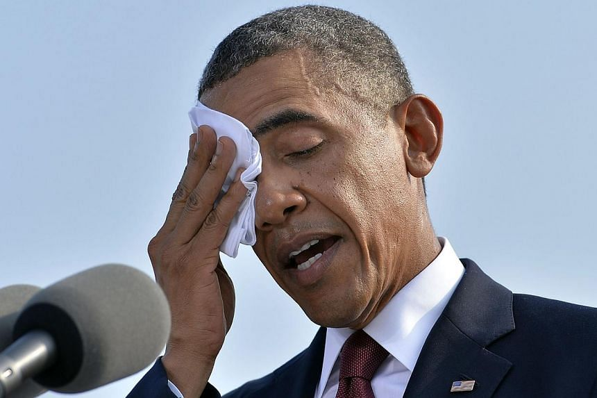 US President Barack Obama wipes his brow while speaking during a ceremony at the Pentagon Memorial to mark the 12th anniversary of the 9/11 attacks in Washington, DC on Wednesday, Sept 11, 2013. -- PHOTO: AFP