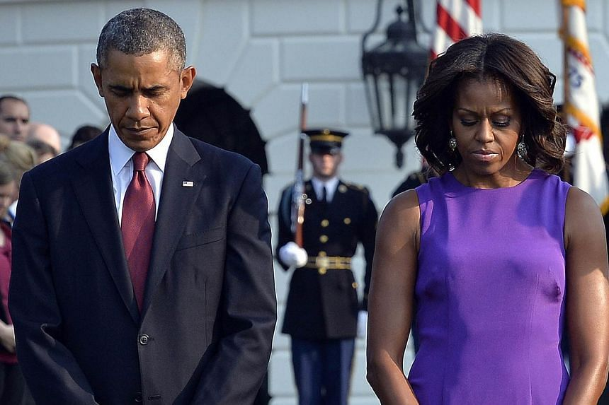 US President Barack Obama and First Lady Michelle Obama observe a moment of silence to mark the 12th anniversary of the 9/11 attacks on the South Lawn of the White House in Washington, DC on Wednesday, Sept 11, 2013. -- PHOTO: AFP