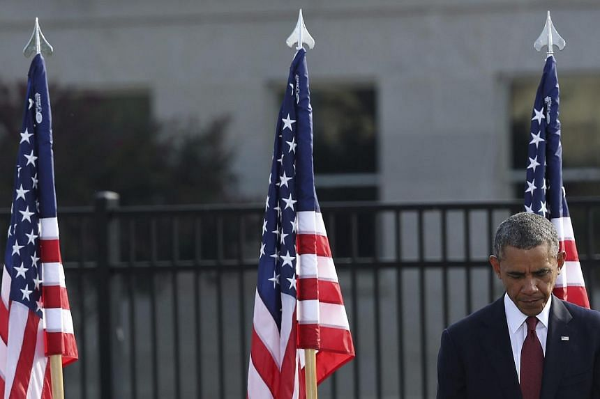 US President Barack Obama bows his head during a prayer at remembrance ceremonies for 9/11 victims at the Pentagon 9/11 Memorial in Washington on Wednesday, Sept 11, 2013. MrObama on Wednesday mourned the lives lost 12 years ago in the Septembe