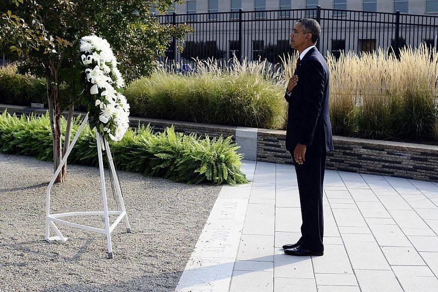 US President Barack Obama pays his respect after placing a wreath at the Pentagon Memorial to mark the 12th anniversary of the 9/11 attacks on the South Lawn of the White House in Washington, DC, on Wednesday, Sept 11, 2013. -- PHOTO: AFP