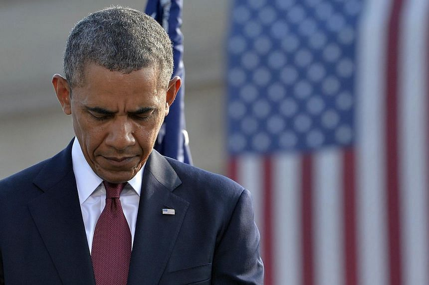 US President Barack Obama bows his head during a ceremony at the Pentagon Memorial to mark the 12th anniversary of the 9/11 attacks in Washington, DC on Wednesday, Sept 11, 2013. -- PHOTO: AFP
