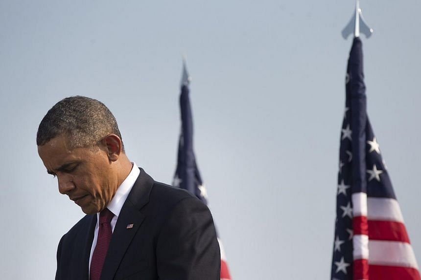 President Barack Obama lowers his head during a moment of silence at the Pentagon on Wednesday, Sept 11, 2013, during a ceremony to mark the 12th anniversary of the 9/11 attacks. -- PHOTO: AP