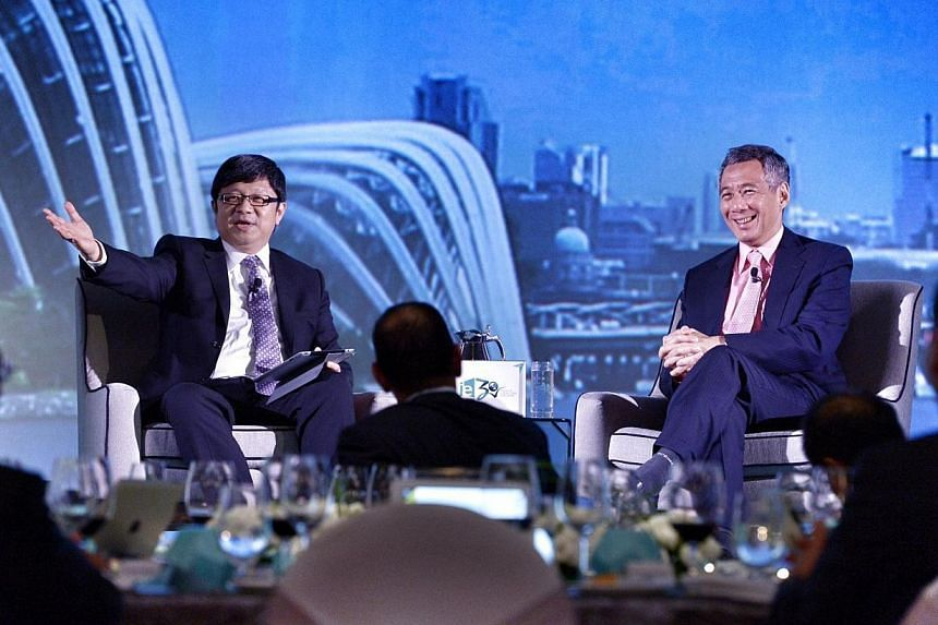 PM Lee at the dialogue with business leaders at IE Singapore's 30th anniversary dinner yesterday at The Ritz-Carlton, Millenia Singapore hotel. Beside him is moderator Robin Hu. -- ST PHOTO: DESMOND WEE