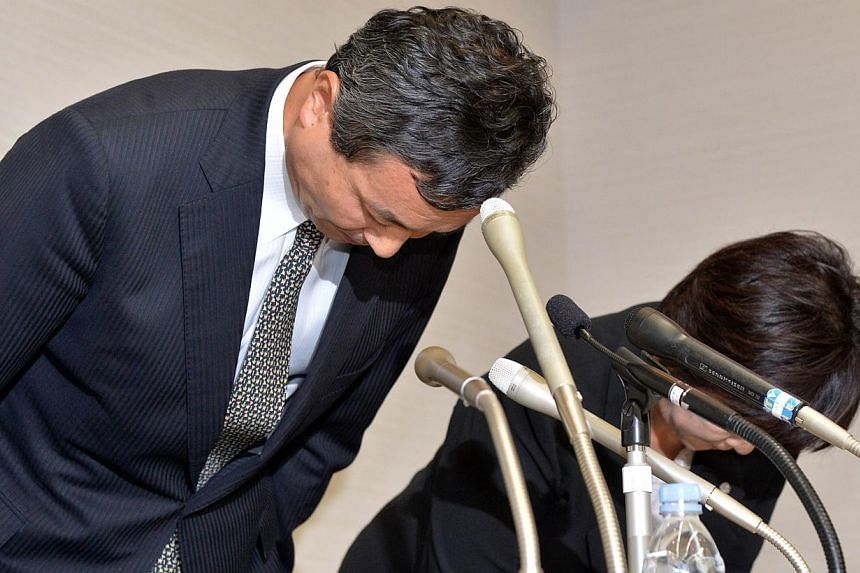 Japan's cosmetics giant Kanebo president Masumi Natsusaka (left) bows his head to apologise over a recall of products blamed for leaving thousands of customers with skin blotches at a press conference in Tokyo on Wednesday, Sept 11, 2013.The he