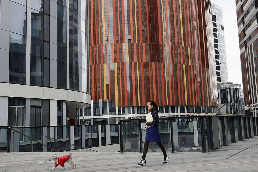 A woman walks with her pet dog at a residential and commercial complex which comprises of shopping malls, office and apartment buildings in a wealthy district in Beijing on Feb 21, 2013. The number of dollar billionaires in China has passed 300 for t