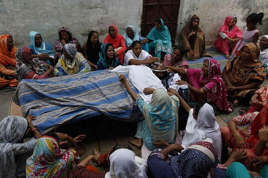 Family members mourn over body of Salamat Maseh, father of two who died after consuming locally made toxic liquor, before his burial outside his house in Karachi.Toxic liquor has killed at least 12 people in central Pakistan, police and h